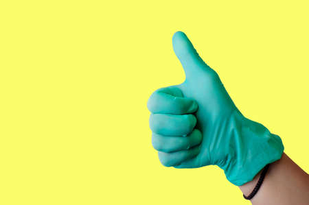 Foto de Female hand in blue latex glove makes thumbs up like gesture isolate on a light yellow background. Medical health concept. Copy space - Imagen libre de derechos