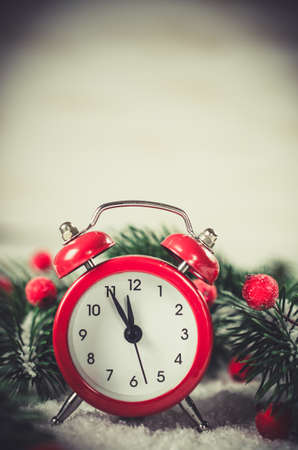 Photo pour Christmas Eve and New Years clock at midnight with fir tree branches covered with snow. Vintage toned image. - image libre de droit