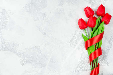 Bouquet of red tulips with ribbon on white background. Spring flowers. Spring background. Greeting card for Valentine's Day, Woman's Day and Mother's Day. Top view, copy space.