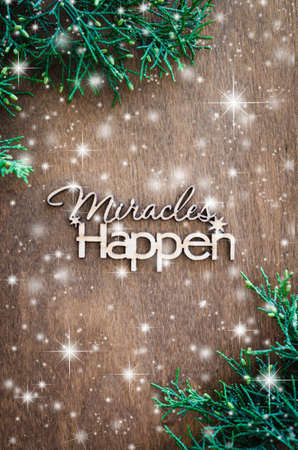 Photo for Inscription miracles happen and fir branches on a wooden background. Concept of inspiration and hope. Top view. Snow effect. - Royalty Free Image