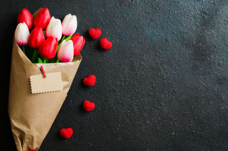 Photo pour Holiday background with spring flowers. Bouquet of tulips and decorative hearts on dark background. Greeting card for Valentine's, Women's or Mother's day. Flat lay, top view, copy space - image libre de droit