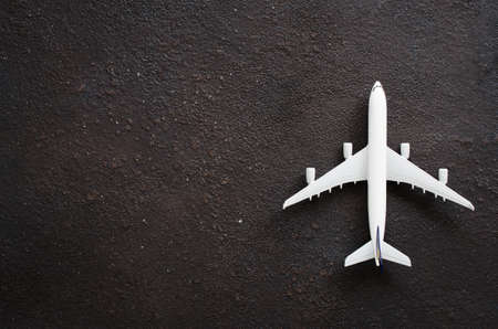 Photo pour Miniature airplane on a dark background. Travel concept. Flat lay with copy space. - image libre de droit