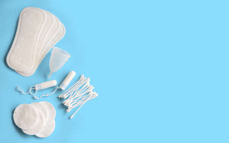 Feminine hygiene accessories. Concept of feminine hygiene during menstruation. Sanitary pad, menstrual cup and tampons, cotton buds and cotton pads on blue background. Flat lay, top view