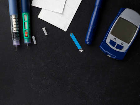 medicine, diabetes, advertisement and health care concept - close up of glucometer with blood sugar test stripe, insulin injection syringes and pills on table.