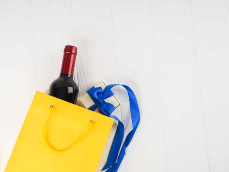 bottle of wine and flowers in the package on wooden background, space for text.