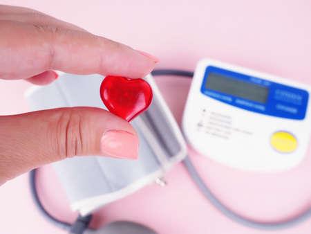 Photo pour Stethoscope, heart shape, blood pressure monitor. female hand holding the heart, blood pressure. - image libre de droit
