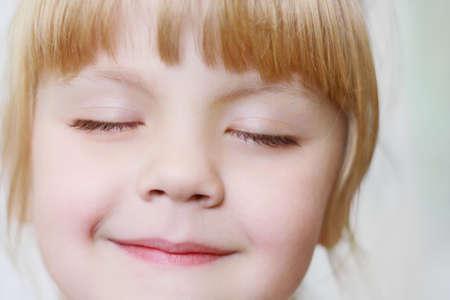 Photo pour Face of a little girl with closed eyes close-up - image libre de droit