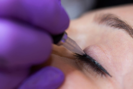 Photo pour Cosmetologist applying permanent makeup on eyes Selective focus and shallow Depth of field - image libre de droit