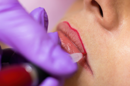Foto de Cosmetologist applying permanent makeup on lips Selective focus and shallow Depth of field - Imagen libre de derechos