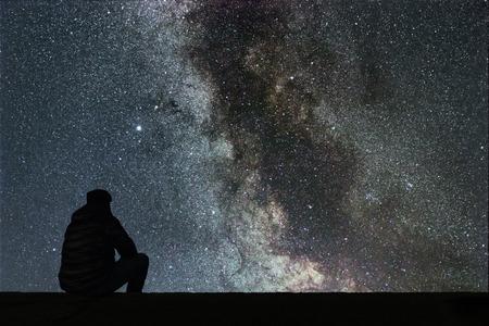 Foto de Milky Way. Night sky with stars and silhouette alone man looking at starry sky. - Imagen libre de derechos