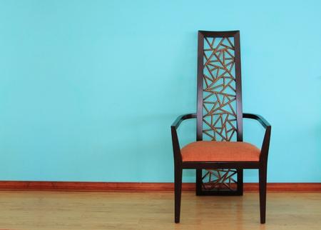 Modern wood chair against a blue wall