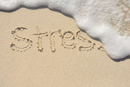 Foto de Relieving Stress, the Word Stress Being Washed Away by a Wave on a Beach - Imagen libre de derechos