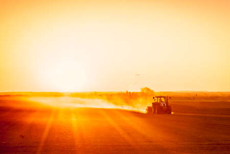 A farmer in a tractor prepares his field as the sun begins to set. The tractor is backlit by the setting sun. The sun is in the upper right corner of the frame, and it is setting behind a low row of hills in the far distance. Seagulls flock behind the tra