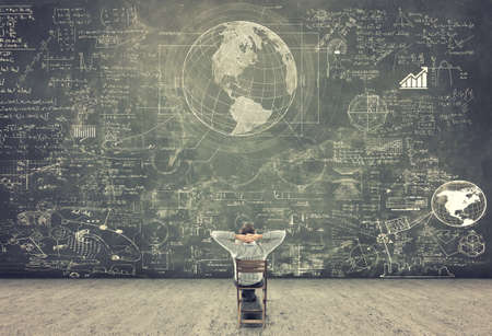 Photo pour Businessman sitting on a chair and studying math formulas on blackboard - image libre de droit