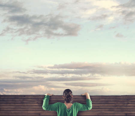 Photo pour The young girl looking over the top of a wood fence. - image libre de droit