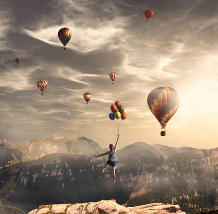 Young woman jumps from mountain cliff and flying with hot air balloons.