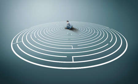 Photo pour Thoughtful man sitting in the middle of a round maze. - image libre de droit