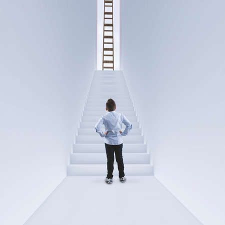 Photo pour Businessman standing in a hallway in front of the stairs . Ladder on top of the stairs. The concept of success . - image libre de droit