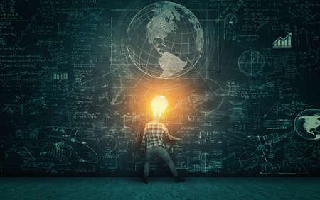 Photo pour Student with lit light bulb as a head solving math problem drawn on blackboard. - image libre de droit