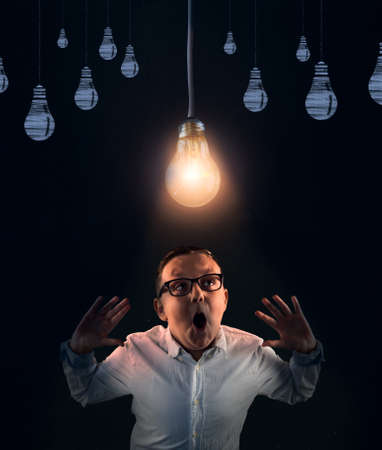Photo for Young man having a brilliant idea . Bright light bulb above head. - Royalty Free Image
