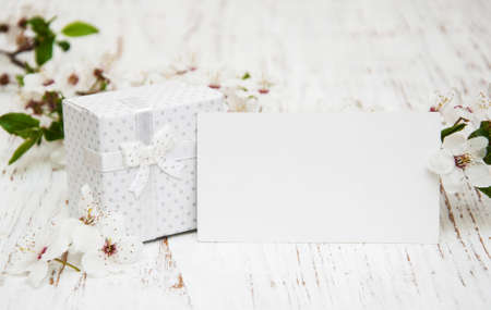 Spring cherry blossom,  gift box and card on a wooden background