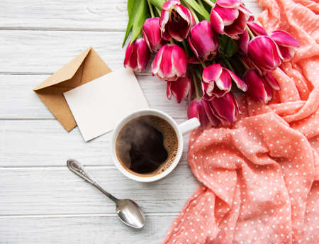 Photo pour Cup of coffee and pink tulips on a old wooden table - image libre de droit