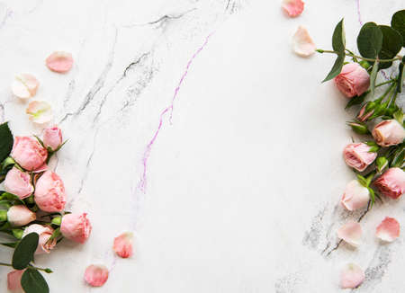 Photo pour Holiday background with pink roses on a white marble - image libre de droit