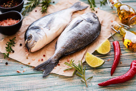 Photo pour Fresh fish dorado. Dorado and ingredients for cooking on a table. - image libre de droit