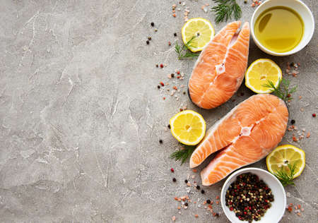 Photo pour Raw salmon steaks and ingredients on a grey concrete background - image libre de droit