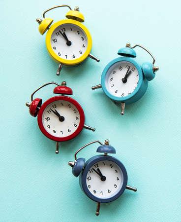 Foto de Flat lay Christmas composition with color alarm clocks  on light blue background. - Imagen libre de derechos