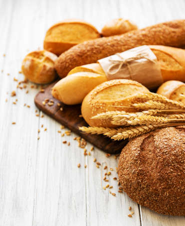 Photo pour assortment of baked bread on white wooden background - image libre de droit