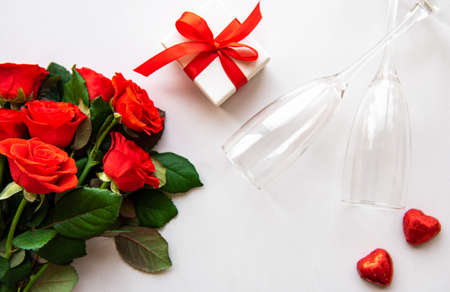Photo pour Red roses and two glasses on a white - image libre de droit