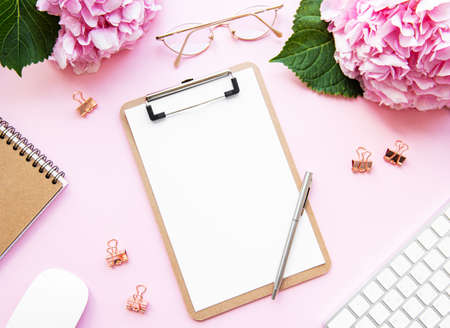 Photo for Home office desk workspace with blank paper clipboard, pink hydrangea flowers bouquet on pink background. Flatlay  - Royalty Free Image
