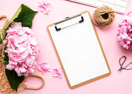 Photo pour Beauty composition with clipboard, hydrangea and accessory on pink background. Top view. Flat lay. Home feminine desk. - image libre de droit