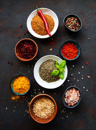 Photo for Various spices in a bowls on black concrete background. Top view copy space. - Royalty Free Image