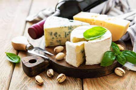 Photo pour Various types of cheese, grapes, wine and snacks on a old wooden background - image libre de droit