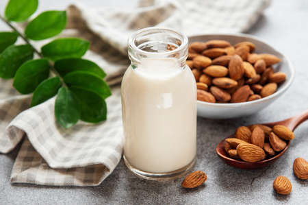 Photo for Glass bottle with almond milk and almonds on the table - Royalty Free Image