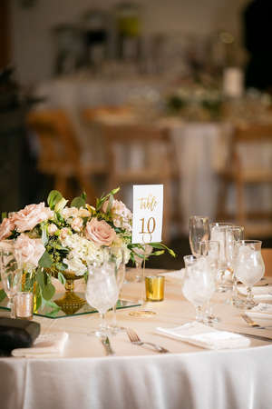 Photo pour Numbered tables set for a wedding ceremony in pink and white and flower center piece - image libre de droit