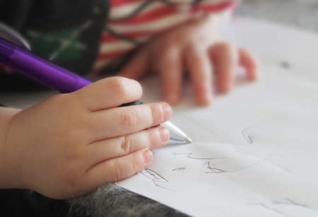 small child s hand writing in notebook