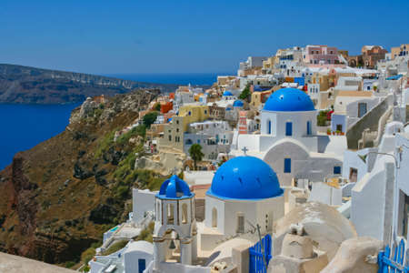 Classic view of Oia on island of Santorini in Greece. Traditional architecture with famous blue belfries.
