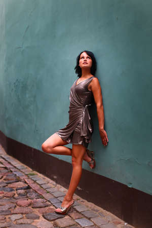 Photo pour Gorgeous woman in beautiful dress is leaning with her back against a wall in sexual and beautiful pose on the street of Old Riga, Latvia - image libre de droit