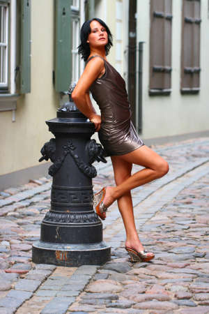 Photo pour Gorgeous woman in beautiful dress is leaning with her back against old column beautiful pose on the street of Old Riga, Latvia - image libre de droit