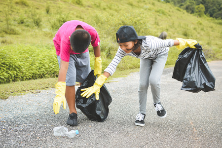 Foto de Children hand in yellow gloves picking up empty of bottle plastic into bin bag ,volunteer concept - Imagen libre de derechos