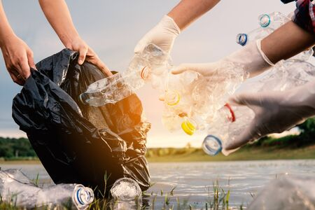 Photo pour Human picking up a bottle plastic in the river, protect environment from a water pollution concept. - image libre de droit
