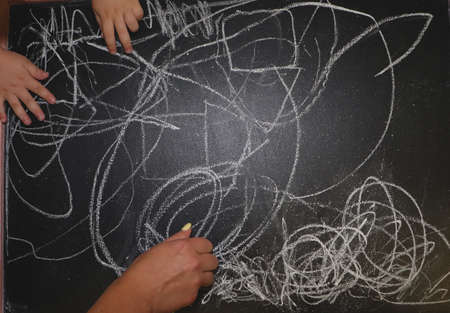 Children draw on a chalkboard in a kindergarten