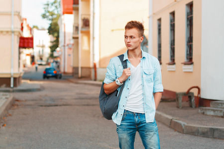 Young handsome man with a backpack in a denim shirt and jeans clothes traveling.