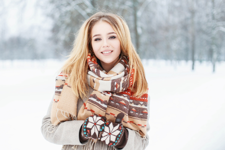 Young beautiful girl with a cute smile in vintage scarf and mittens in winter day
