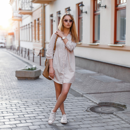 Photo for Beautiful young fashion girl in sunglasses, handbags and sneakers standing on a sunset background - Royalty Free Image