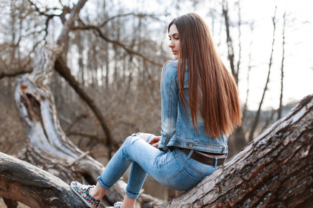 Young beautiful girl in denim jacket and jeans sits on a tree and dreams.