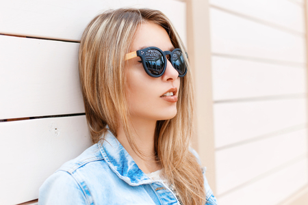 Photo pour Close-up portrait of a beautiful young girl in sunglasses and denim jacket on the beach near the wooden wall - image libre de droit